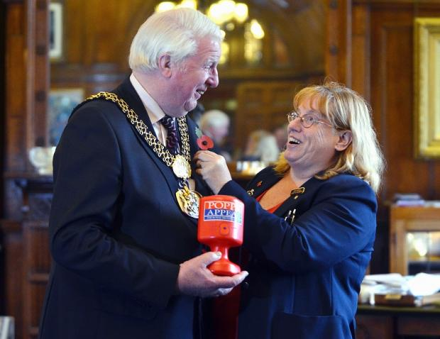 The Lord Mayor of Bradford Coun Dale Smith receives the district's first poppy from British Legion volunteer Barbara Allsopp today
