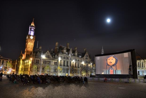Crowds enjoy an animated film on the inflatable cinema in City Park