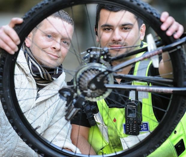PC Luke Eliasz and Michael Carr from the Bridge project look at one of the bikes