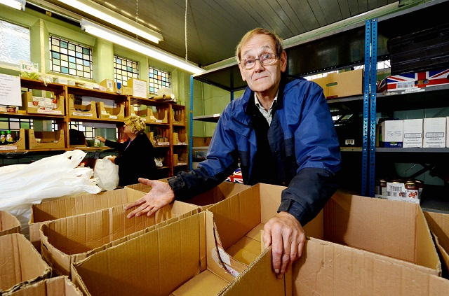 Foodbank co-ordinator Ken Leach with empty shelves and boxes – appealing for donations