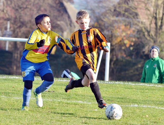 Idress Akhtar of Albion Sports under-12s and Bradford Park Avenue Lizards opponent Lewis Melvin battle for possession