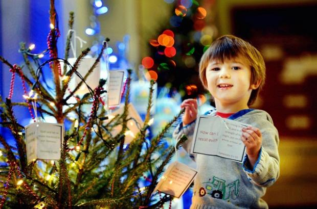 Three-year-old Reuben Smith putting the finishing touches to a Chrsitmas tree at St Christopher's Church in Holme Wood