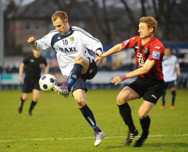 Guiseley striker James Walshaw holds off Histon's Grant Roberts