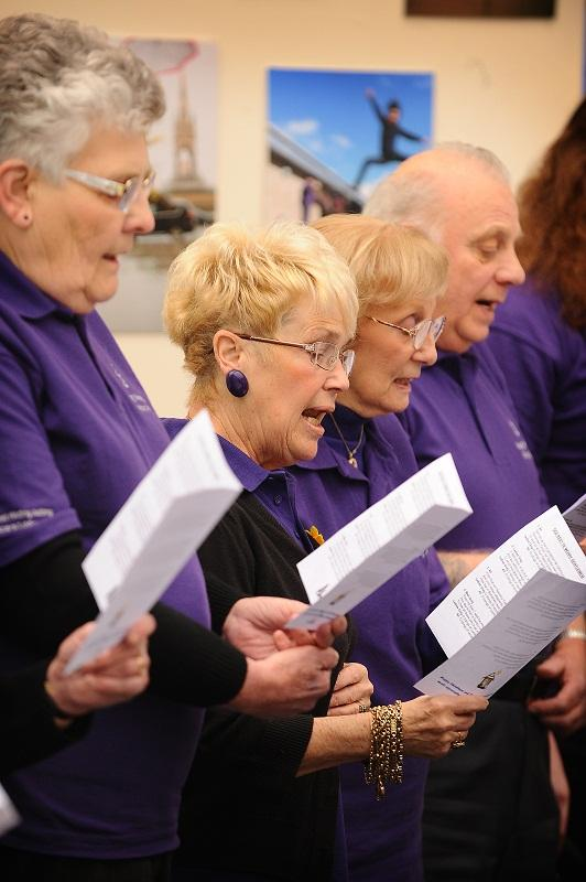 Happy Memories singers perform in the atrium of Bradford University