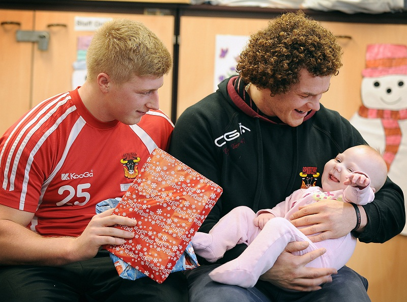 Bulls players Danny Addy and Jamie Langley give presents to BRI patient Brooke Mitchell