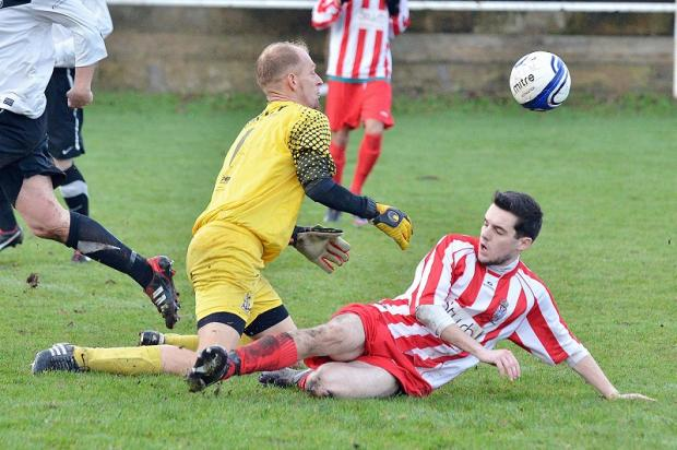 Adam Bulmer of Thornton United challenges White Eagles keeper Andy Smith
