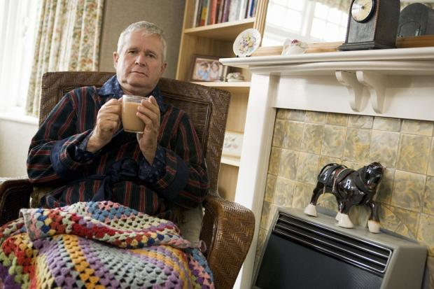 An elderly man has a hot drink to help keep warm