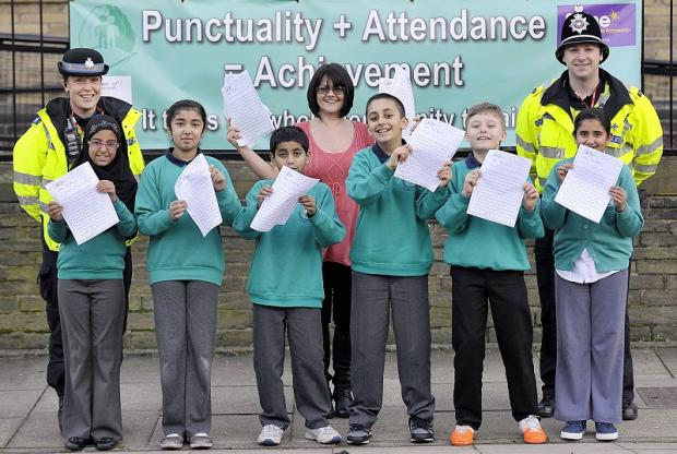 CONCERNS: Year Five and Six pupils from Frizinghall Primary with (from left) PCSO Cath Elder, deputy head Lisa Wetherall and PC Matt Jerram after designing a banner