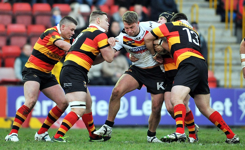 Elliott Whitehead finds himself outnumbered as four Dewsbury players latch on to him