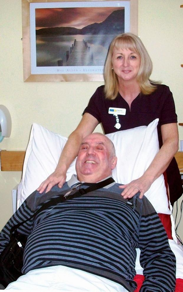 Volunteer complementary therapist Denise Shaw with patient Roland Bell