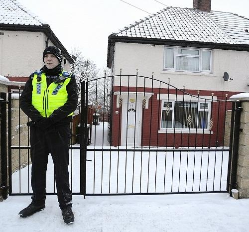 A police officer stands guard outside the house in Lynfield Drive