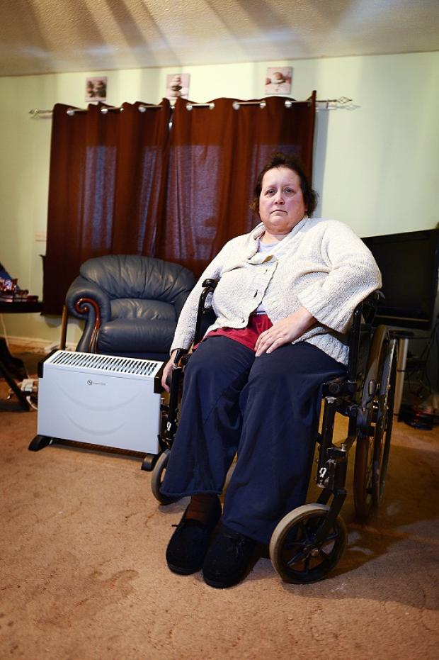 Disabled mother Anne Woods with an electric radiator in her front room