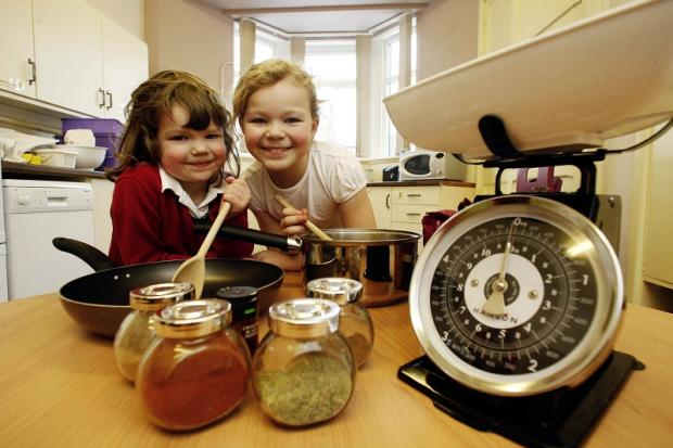 Lees Primary pupils Isabelle Lockyer, four, left, and her sister Amy, eight, get ready for the curry night