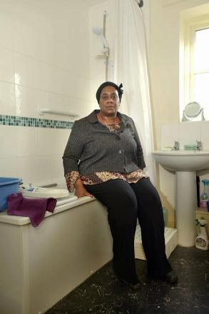 Denise Brown in the bathroom of her home which she says can only get tepid water from the taps