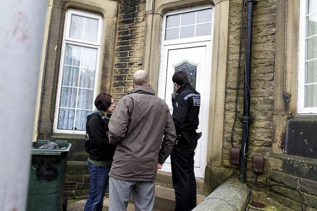 Police serving an injunction at a house in Keighley during yesterday's operation to target gang activity