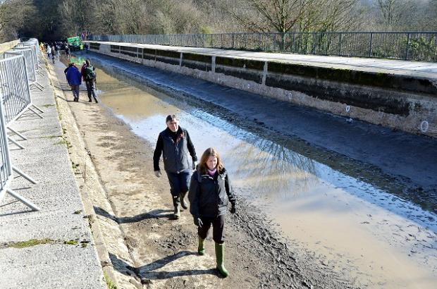 Visitors cross the Dowley Gap Aqueduct near Bingley yesterday after it had been drained for repairs