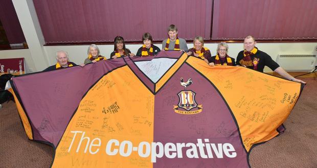 Friends of Bradford City – Mark Neale, Julie Stainthorpe, Shena Shackleton, Jean Calvery, Julie Neale, and Iain Vitty with Beverley Pitts from the Co-op store in Wibsey and former City player Ian Ormondroyd (centre) – receive the giant shirt