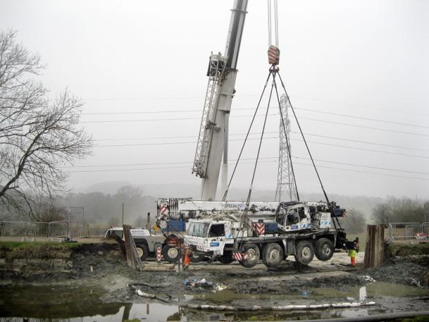 The 90-ton crane is winched from the canal