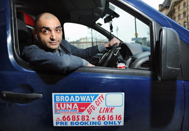 Saj Akbar, of Broadway Luna, with his minicab sign displayed on the door