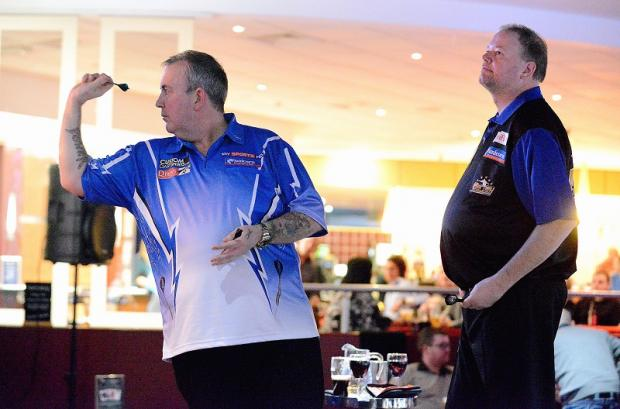 Phil Taylor lines up another shot as Raymond van Barneveld looks on