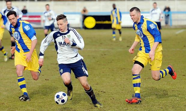 Guiseley's Wayne Brooksby gives Solihull Moors' Karl Broadhurst, left, and Danny Spencer the slip