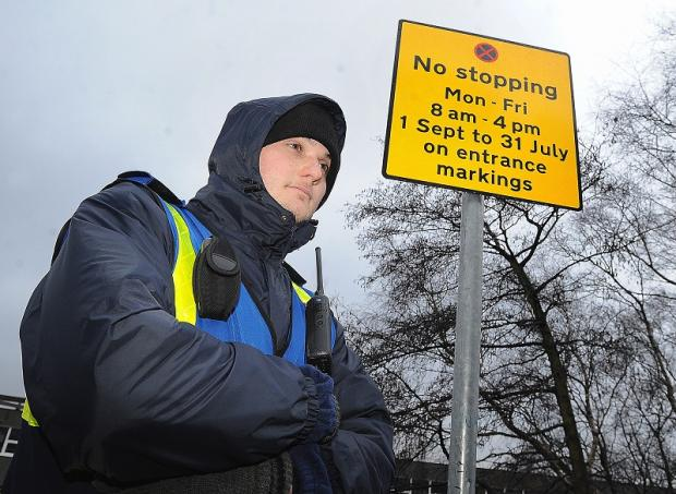 A Council warden monitors car parking outside Carlton Bolling College