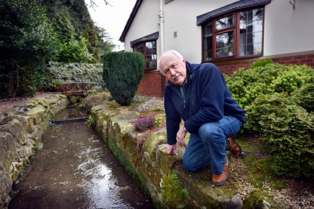 Peter Roberts with the water course running through his garden