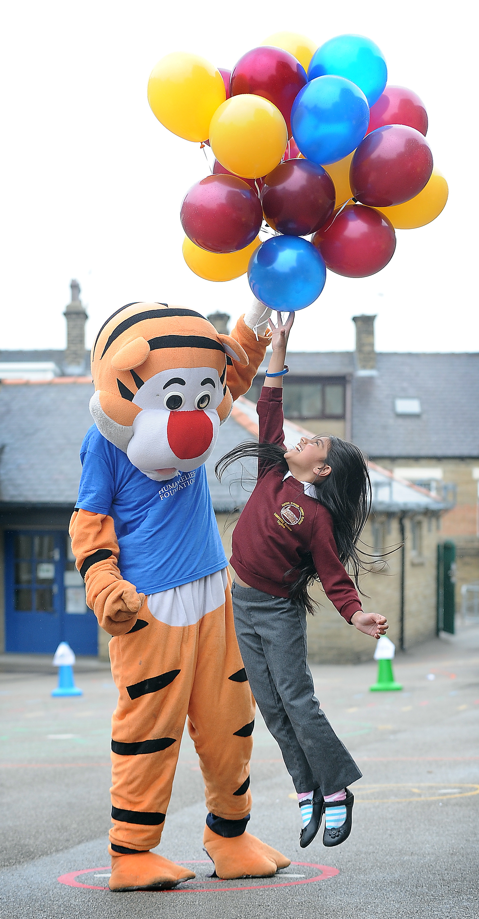 Eshal Ahmed tries to reach balloons being released by Tigger, visiting Horton Grange Primary School to help at a balloon release for Refugee Week