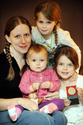 Lucy Deakin with baby Eliza, who is receiving treatment for eye cancer, and her sisters Megan and Freya