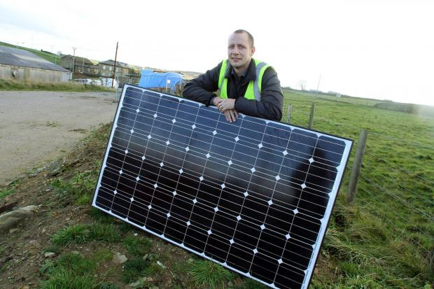 Bradford Telegraph and Argus: Julian Haddock with a solar panel for the Denholme Business Centre