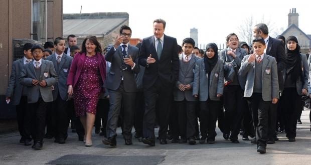 Sajid Hussain Raza (centre) welcomes David Cameron to Kings Science Academy in March 2012