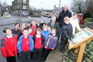 Bradford Telegraph and Argus: Charlie Driver and Laila Heslop, of Hothfield Junior School's archaeology club, look at the information board with Councillor Andrew Mallinson (centre) David Mason of Silsden Local History Group, children from the school and headteacher James Procter