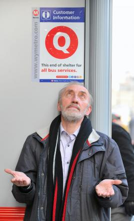 Coun Geoff Reid at the new sign helping queues at the city centre bus shelters