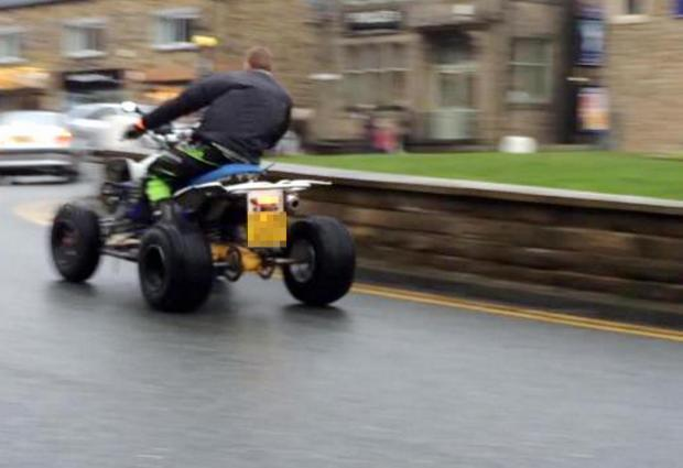A quad biker drives on the road in Baildon