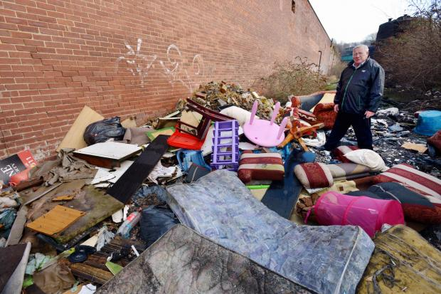 Councillor Mike Ellis looks at fly-tipping on Birksland Street, Bradford