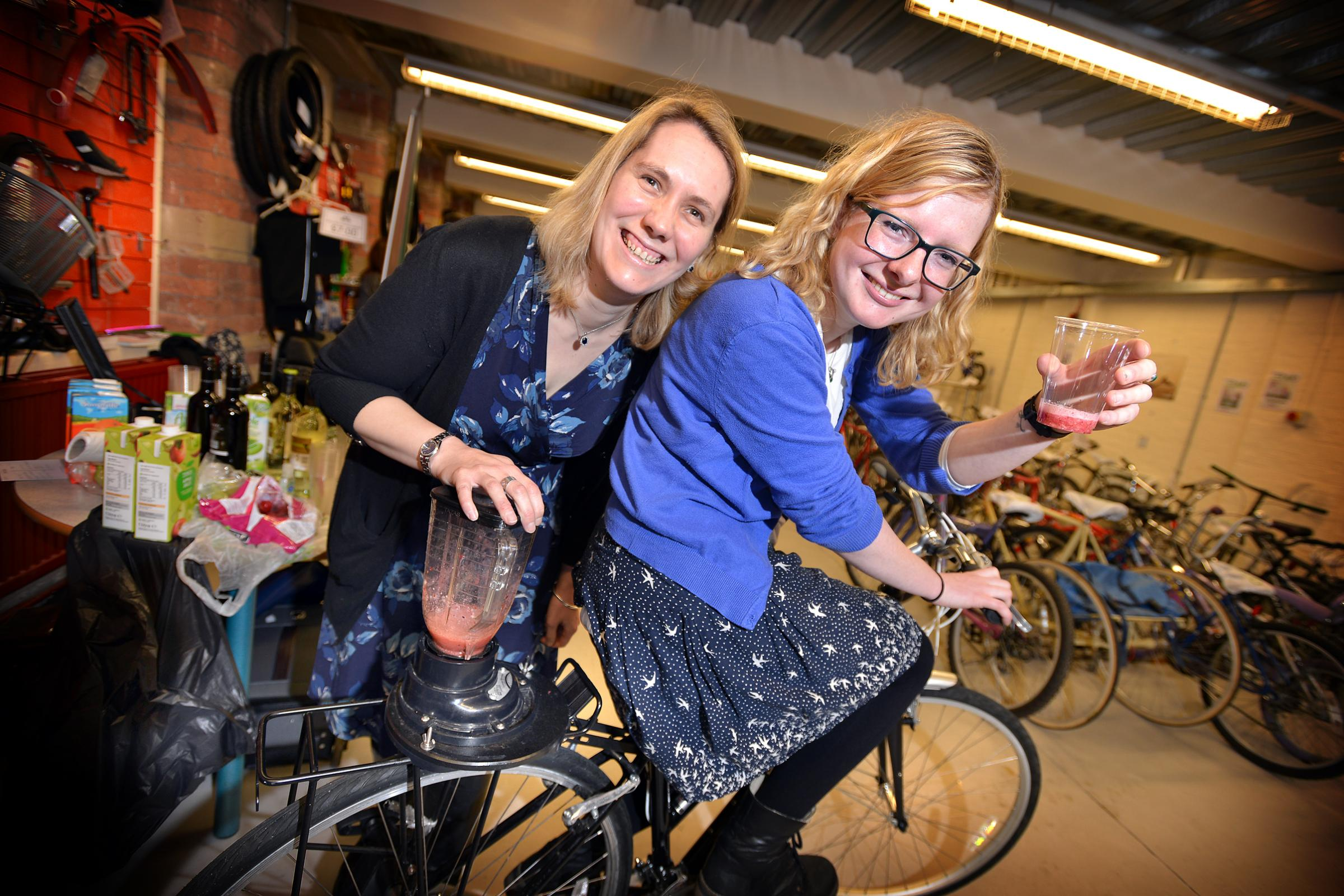 Joanna Ward (left) and Jennie O'Hara try the pedal-powered smoothie machine