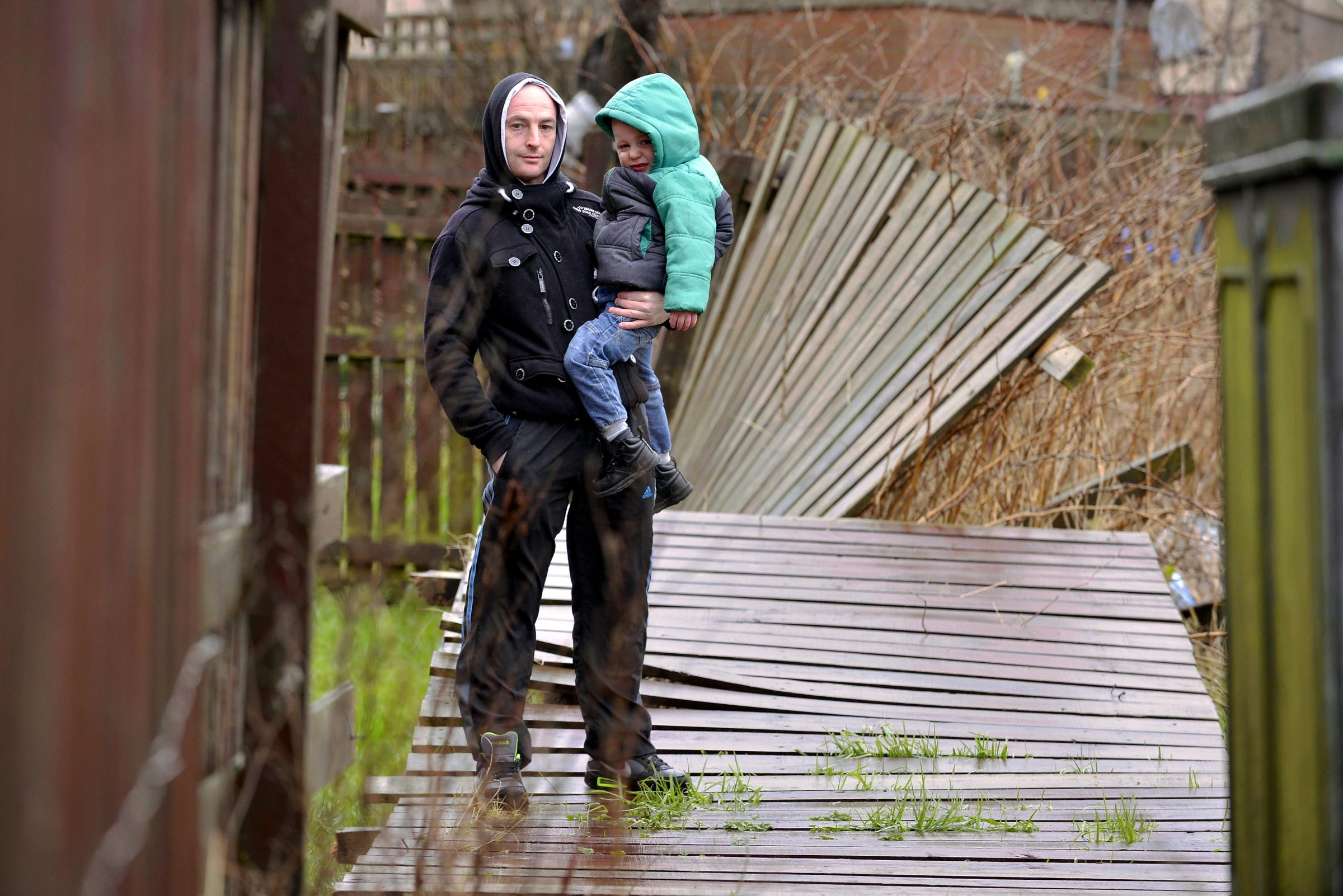 CONCERN: Robert Whitford and his son Codie, three, pictured at their home in Allerton next to a broken fence