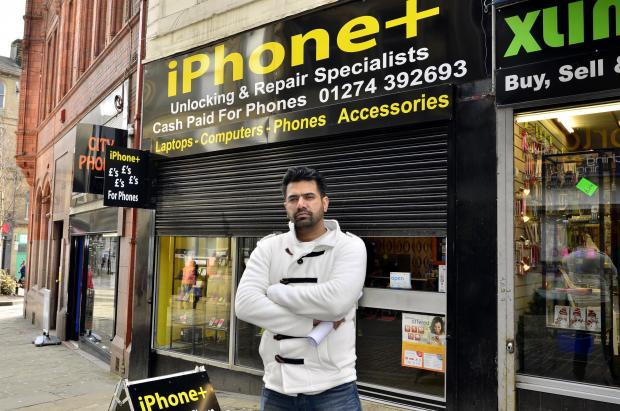 Owner of iPhone Plus, Irfan Qaiser, outside his shop in Ivegate, with the security shutters that are not within planning rules