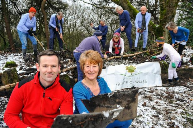 Damart's senior and ecommerce manager Ben Phillips with chair of the Friends of Prince of Wales Park Ruth Leeman with volunteers in the background working in their Damart thermals