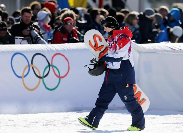 Jamie Nicholls walks past the Olympic rings symbol after competing in the slopestyle snowboarding final in Sochi