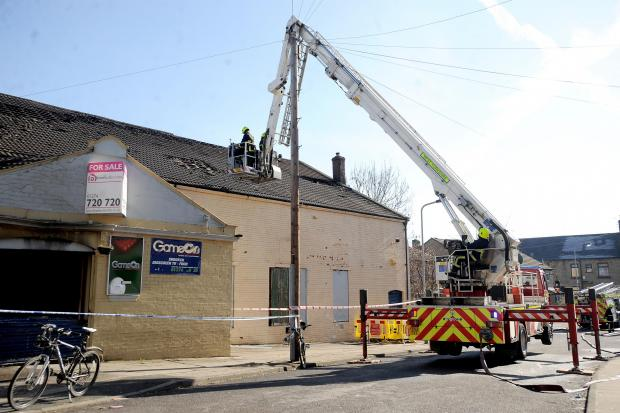 Firefighters damp down after the Game On Leisure Centre fire