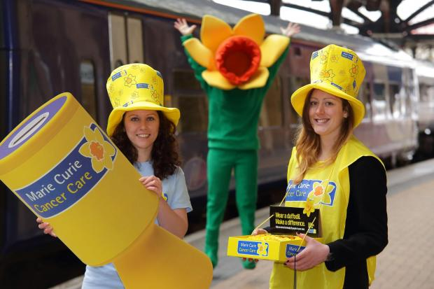 Natalie Atherley from Marie Curie and Becky Daniels from Northern Rail celebrate the partnership with Daffy, the Marie Curie mascot