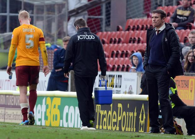 A glum-faced Phil Parkinson  looks on as Andrew Davies limps off against Stevenage