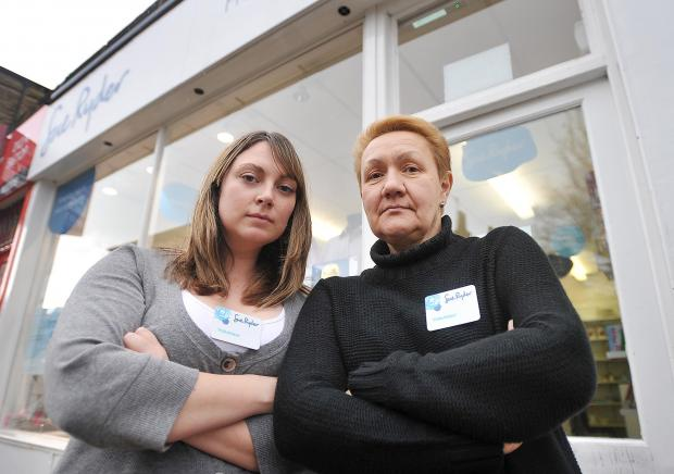 Volunteers Victoria Read and Olena Stavytska at Bingley's Sue Ryder charity shop. Inset, damage to a door