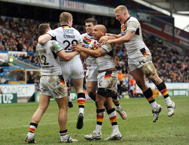 Bulls players celebrate an Adam O'Brien try during their victory at Huddersfield early last season, which was later followed by another b