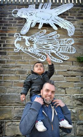 Paul Slater aka Fabric Lenny with Mohammed Ayaan Ali, three, in front of the pieces of art on Midland Road as part of the Manningham Together project