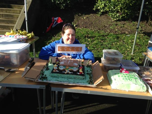 Organiser Linda Bussey shelters behind the parkrun birthday cake