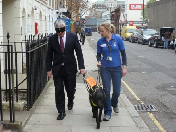 David Ward is led by Sky and a Guide Dogs trainer
