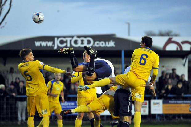 Bradford Telegraph and Argus: Guiseley's Danny Hall goes flying as he tanngles with the Gainsborough Trinity defence
