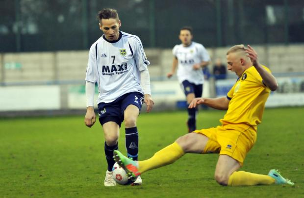 LOCAL SUPPORT: Guiseley's Wayne Brooksby is tackled during his side's midweek win over Gainsborough. Park Avenue boss John Deacey is right behind their play-off bid